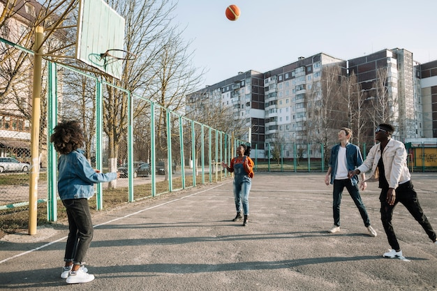 Group of teenagers playing basketball together