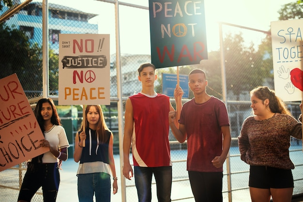 Group of teenagers protesting demonstration holding posters