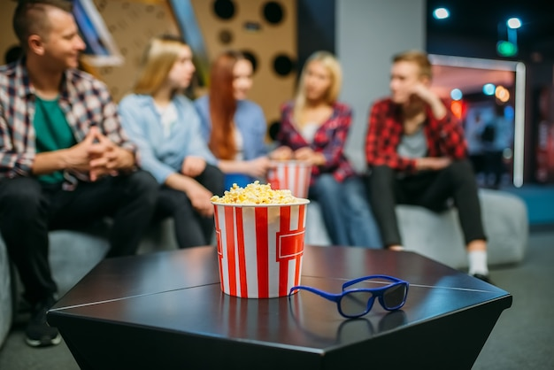 Group of teenagers relax on the couch and waiting for showtime in cinema hall. male and female youth sitting on sofa in movie theater, popcorn on the table