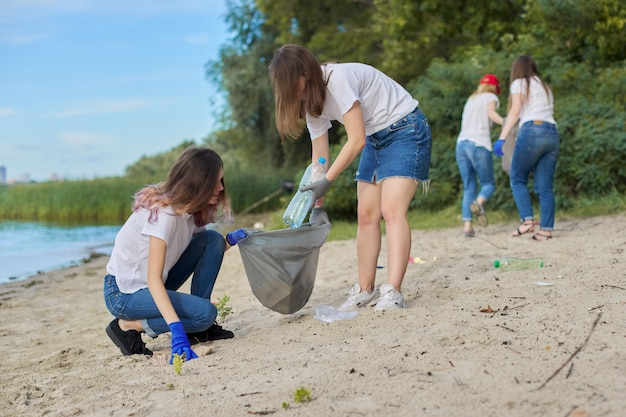 Group of teenagers on riverbank picking up plastic trash in bags