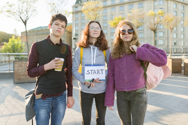 Group teenagers with notepad with handwritten word start