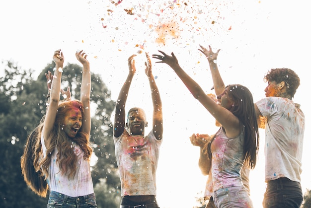 Group of teens playing with colors at the holi festival, in a park