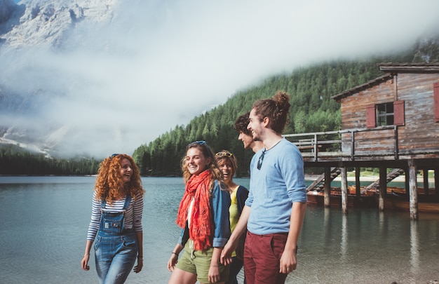 Group of teens spending time on the lake beach