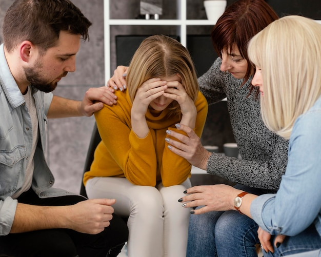 Group therapy comforting woman