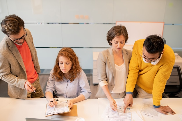 Group of thoughtful concentrated young multi-ethnic business analysts reading papers and examining information together in office