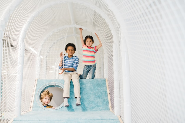 Group of three adorable kids of different ethnicities looking at you while enjoying play at leisure center