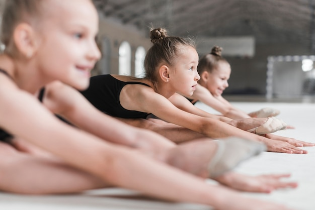 Group of three ballerinas girls sitting on floor stretching forward on dance floor