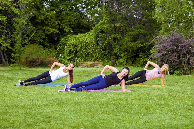 Group of three beautiful healthy slimy woman doing exersices on the green grass in the park, side palnk, looking at camera with toothy smile. outdoor morning, sport lifestyle wellness and weight loss.
