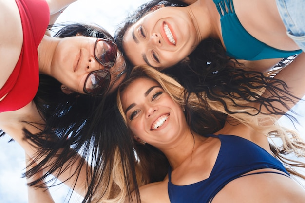 Group of three beautiful young girls having fun on the beach. close up picture of cheerful women from below. smiling company
