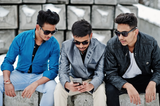Group of three casual young indian mans in sunglasses posed against stone blocks and looking at mobile phone.