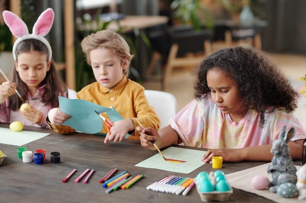 Group of three cute little friendly children of various ethnicities sitting by table in home environment and preparing presents for easter