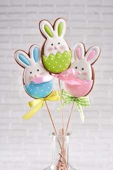 Group of three easter bunny cookies on stick in vase