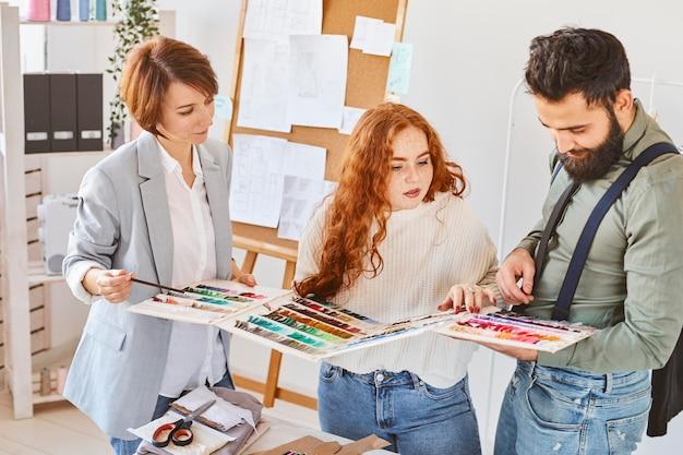 Gruppo di tre stilisti che lavorano in atelier con tavolozza dei colori