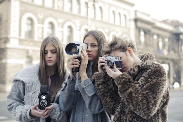 Gruppo di tre amiche che scattano foto con le loro fotocamere