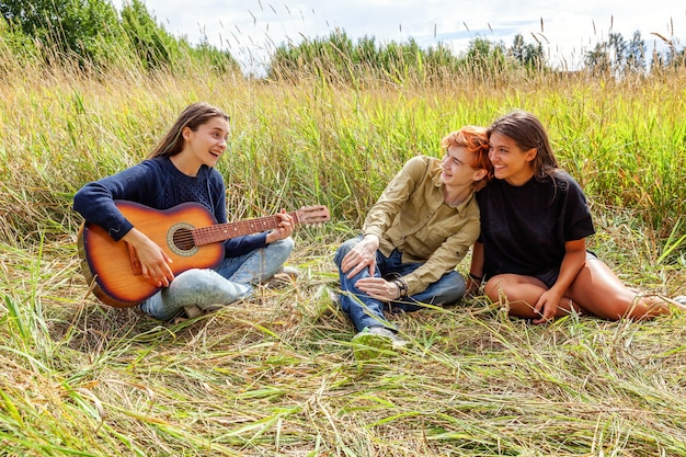 Group of three friends boy and two girls with guitar singing song having fun together outdoors
