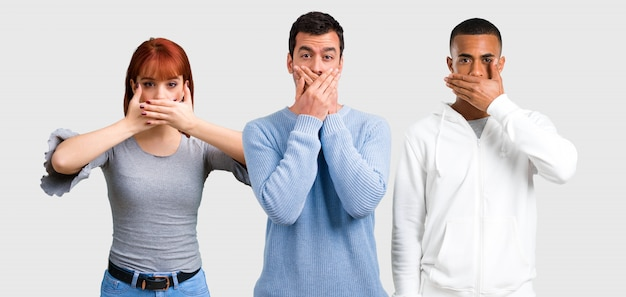 Group of three friends covering mouth with hands