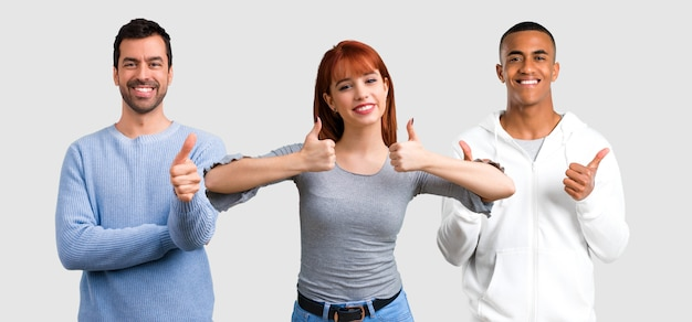 Group of three friends giving a thumbs up gesture and smiling