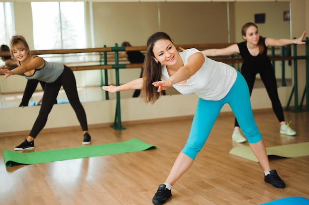 Group of three girls doing exercises in the gym