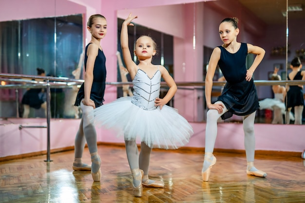 Group of three little ballet dancers in tutu standing in poses on the dance hall. young ballet dancers in a studio with wooden floor and mirrors.