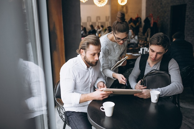 Group of three people working on a project on a tablet in a cafe