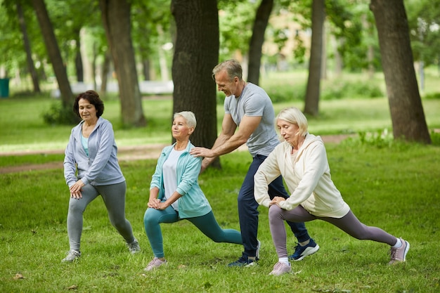 Group of three senior women spending morning together in park doing exercises with their trainer helping them