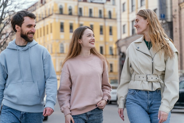 Group of three smiley friends outdoors in the city
