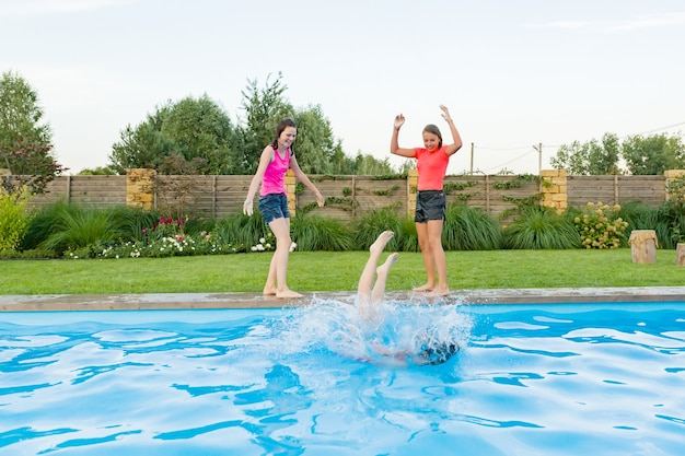 Group of three teenage friends having fun in swimming pool