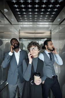 Group of three young intercultural office managers with smartphones calling clients inside elevator during coffee break