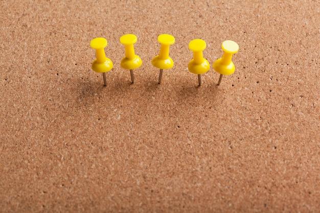 Group of thumbtacks pinned on corkboard background
