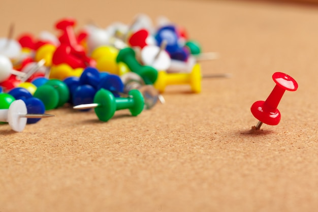 Group of thumbtacks pinned on corkboard close up. school or business