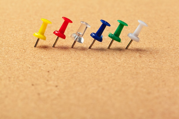 Group of thumbtacks pinned on corkboard in a row close up view