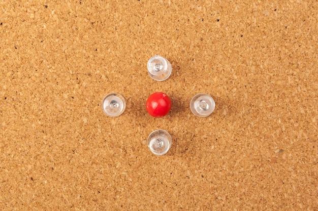Group of thumbtacks pinned on corkboard