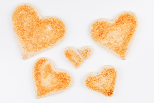 Group of toasted bread hearts with one broken heart together on white background