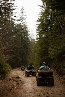 A group of tourists on atvs go through the forest. dirty atvs drive off-road.