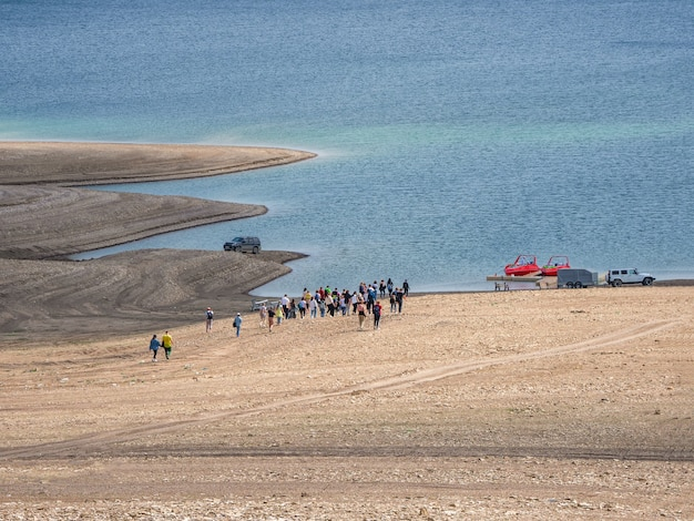 A group of tourists goes to get into the boats. remote view. sulak reservoir, dagestan.