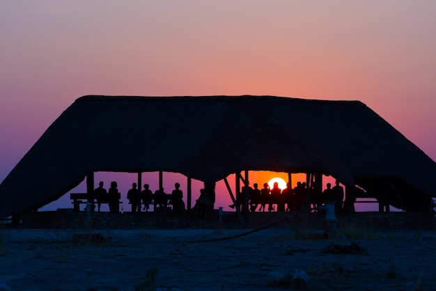 Group of tourists watching colorful sunset under shelter
