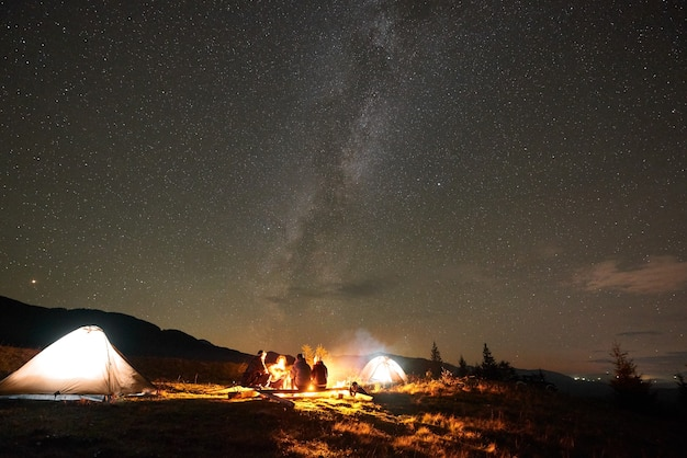 Group of tourists with guitar by burning bonfire under dark starry sky with milky way constellation.