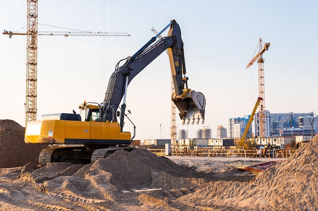 Группа башенных кранов и силуэт экскаватора на строительной площадке, поверхность закатного неба. жилой многоэтажный комплекс будущего