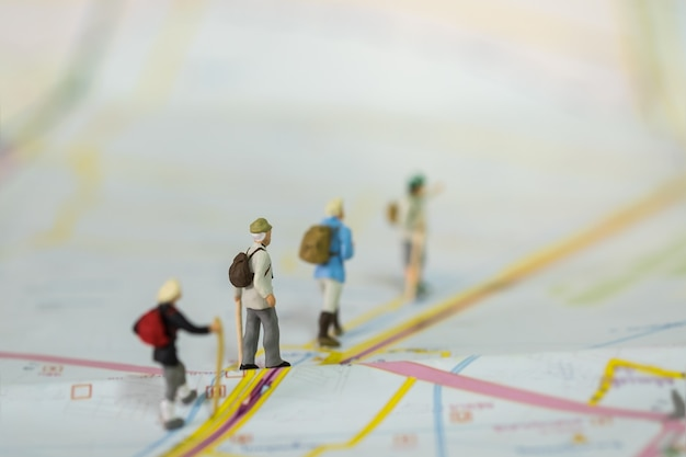 Group of traveler miniature figure people with backpack walking on map