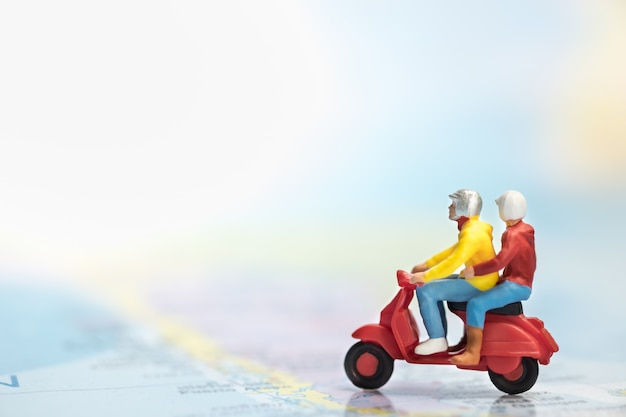Group of traveler miniature figures ride motorcycle / scooter on world map.