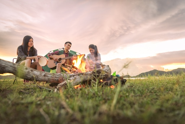 Group of travelers camping and doing picnic and playing music together.