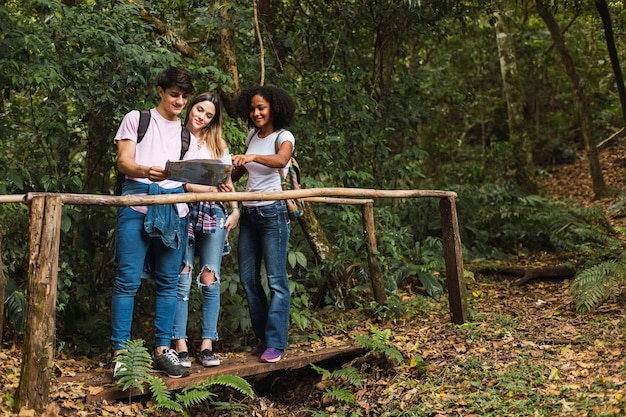 Group of travelers looking at the map in the jungle
