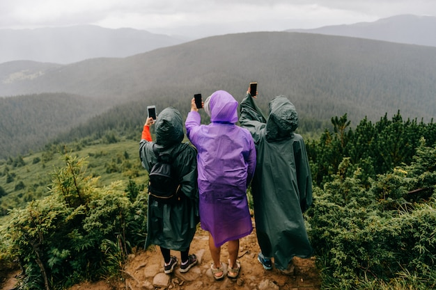 Group of travelers in raincoats in mountain take photos of nature on phones.