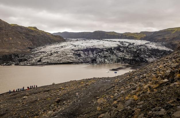 Gruppo di viaggiatori nel ghiacciaio solheimajokull, islanda durante un clima freddo
