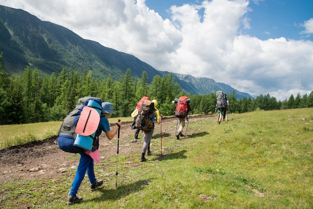 Group of travelers with backpacks walk along a trail towards a mountain ridge by sunny day