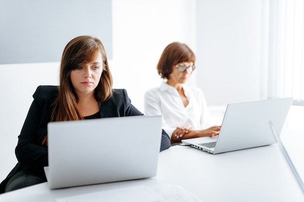 Group of two business women working on laptops at office