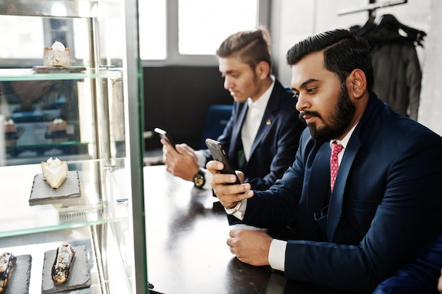 Group of two indian businessman in suits sitting on cafe and looking at phones.