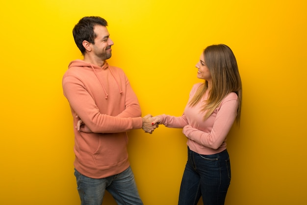 Group of two people on yellow background handshaking after good deal
