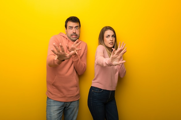Group of two people on yellow background is a little bit nervous and scared