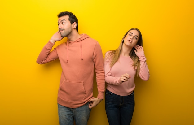 Group of two people on yellow background listening to something
